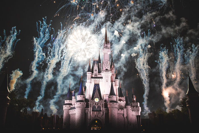 Disney magic kingdom in Orlando castle lit up with light and fireworks a top family travel destination