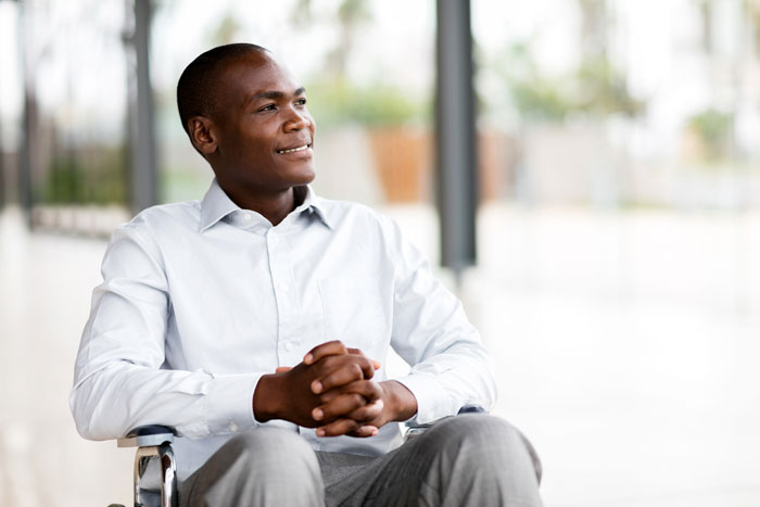 young African American lawyer with disabilities in wheelchair smiling thoughtfully out the window